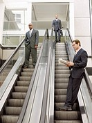 Businessmen on escalators