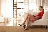 Young woman using laptop in living room (thumbnail)