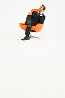 Pensive businessman sitting in chair on white background