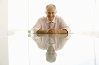 Businessman sitting at table smiling portrait (thumbnail)
