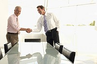 Businessmen shaking hands by conference table