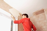 Man scraping paint off wall in unrenovated room low angle view