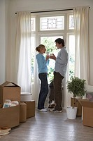 Couple standing by window surrounded by boxes (thumbnail)