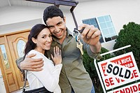 Homeowners standing in front of house with Sold sign holding key portrait (thumbnail)