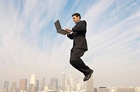 Business man using laptop mid_air above city