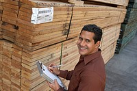 Worker taking notes on clipboard by stack of wood in warehouse elevated view