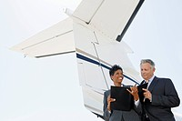 Businesspeople standing below wing of private jet low angle view