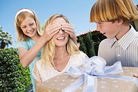 Daughter covering eyes of mother who's receiving Gift from her Children outside