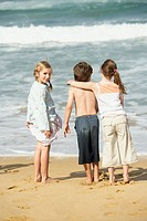 Three children standing at water edge on beach back view (thumbnail)
