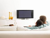 Rear View of couple on sofa watching TV