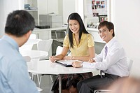 Two office workers sitting at table in office smiling at colleague (thumbnail)
