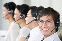 Row of customer service representatives wearing telephone headsets in office head and shoulders (thumbnail)
