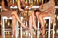 Stylishly dressed women sitting legs crossed at bar drinking low section