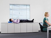 Businessman sleeping on office cabinets near woman working (thumbnail)