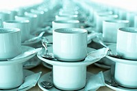 Rows of stacked teacups and saucers close-up (thumbnail)