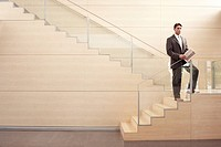Businessman holding newspaper standing on Stairs