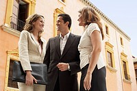 Two businesswomen and one businessman standing outdoors low angle view