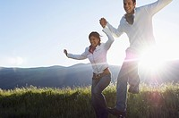 Young couple running and jumping in mountain field (thumbnail)
