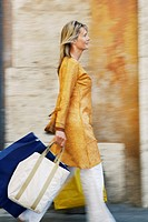 Woman Walking with Shopping Bags on street in Rome side view