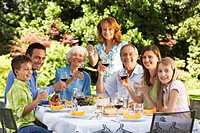 Family sitting at table for lunch in back yard portrait