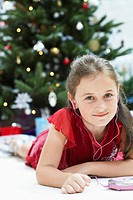 Little Girl lying down by christmas tree Listening to CD Player portrait