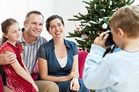 Boy taking photo of sitter mother and father by christmas tree
