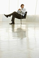 Businessman sitting in empty conference room