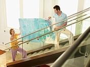 Couple moving modern painting up stairs elevated view