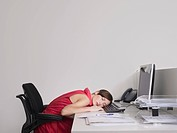Female office worker asleep at desk in office