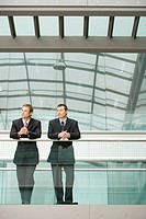 Two Businessmen Leaning at Railing front view