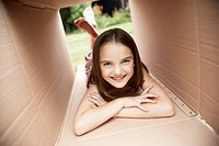 Girl in backyard lying in cardboard box portrait