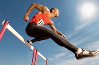 Male athlete jumping hurdle mid air