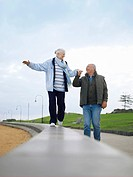 Senior couple walking on wall holding hands