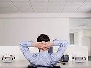 Male office worker relaxing at desk
