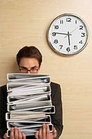 Businessman holding files standing under clock half length