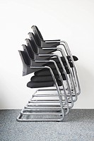 Stack of office chairs against wall
