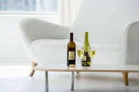 Wine glasses and bottles on coffee table in living room
