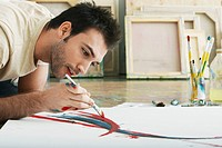 Man painting on canvas on studio floor
