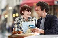 France Paris Couple reading map sitting outside cafe