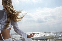 Young woman meditating on beach facing ocean back view (thumbnail)