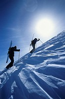 Skiers hiking to mountain summit