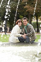 Couple sitting on edge of fountain view past water jets