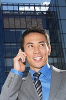 Smiling Businessman Using Cell Phone outside building (thumbnail)