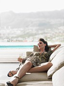 Woman reclining on sofa with champagne on balcony (thumbnail)