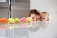 Young girl and boy peeking over counter at row of cupcakes high section