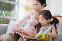 Mother sitting with daughter on sofa reading a book