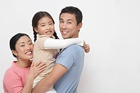 Family portrait of father holding daughter mother hugging on other side side view