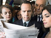 Commuters standing on train reading newspaper over shoulder (thumbnail)