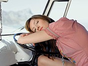 Woman Resting on Steering Wheel in van half length