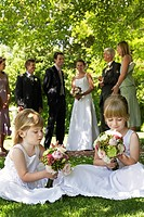 Two young girls sitting on lawn holding bouquets bride and groom in background